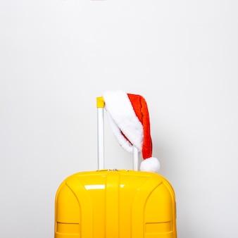 Żółta plastikowa walizka w czerwonej czapce świętego mikołaja