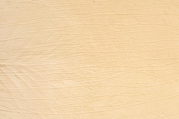 Żółta plaża tekstury piasku na plaży do użytku w tle.