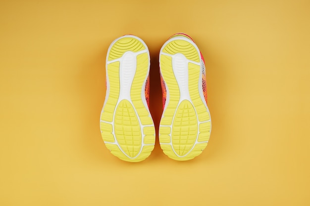Żółta podeszwa tenisówki na żółtym tle. minimalistyczna koncepcja, styl sportowy, widok z góry