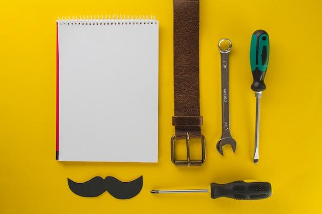 Żółta powierzchnia z pustym notatnikiem i narzędziami na dzień ojca