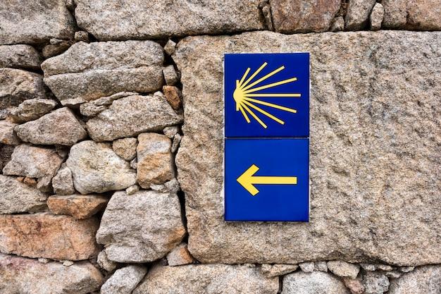Żółta przegrzebek skorupa, turystyczny symbol camino de santiago pokazuje kierunek na camino norte w hiszpania.