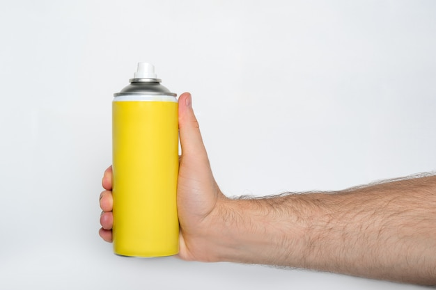 Żółta puszka z rozpylaczem do rozpylania na męskiej dłoni.