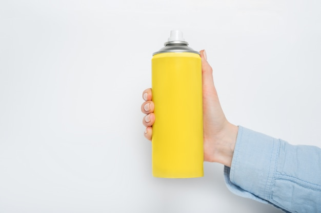 Żółta puszka z rozpylaczem do rozpylania w kobiecej dłoni.