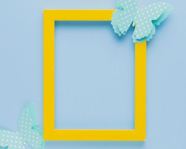 Żółta ramka ozdobiona wycięciem na motyle