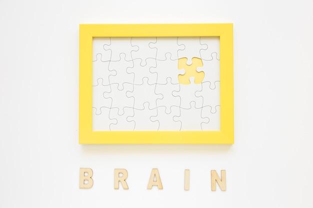 Żółta ramka z brakującym elementem układanki w pobliżu słowa mózgu