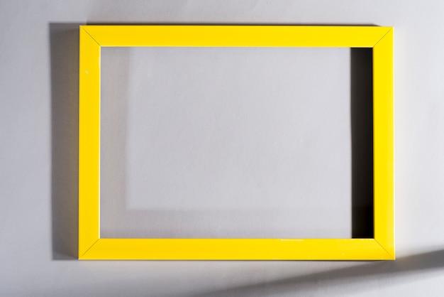 Żółta ramka z cieniami na szarym stole. modne kolory 2021.