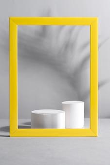 Żółta ramka z cieniami palm i białymi geometrycznymi podiumami na szarym stole. modne kolory 2021.