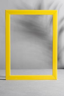 Żółta ramka z cieniami palm na szarym stole. modne kolory 2021.