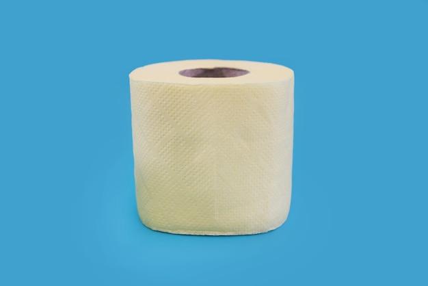 Żółta rolka papieru toaletowego na niebieskim tle.