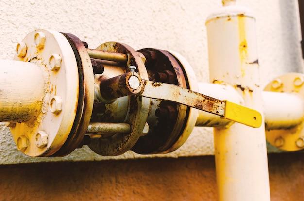 Żółta rura gazowa z dźwigiem biegnie wzdłuż fasady nowego wielokondygnacyjnego budynku.