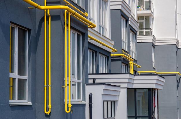 Żółta rura gazowa z odpowietrznikiem na fasadzie wielokondygnacyjnego budynku. gaz ziemny do użytku domowego, gazociąg.