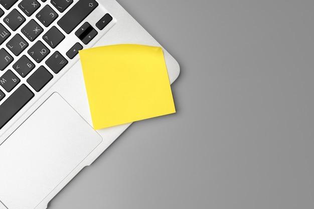 Żółta samoprzylepna notatka na otwartym laptopie na szarym tle