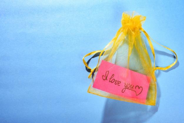 Żółta satynowa torebka z kawałkiem różowego papieru i napisem i love you na niebieskim polu