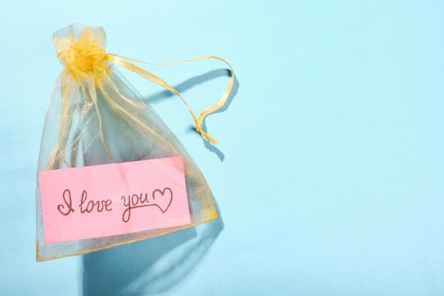 Żółta satynowa torebka z kawałkiem różowego papieru i napisem i love you na niebieskim tle