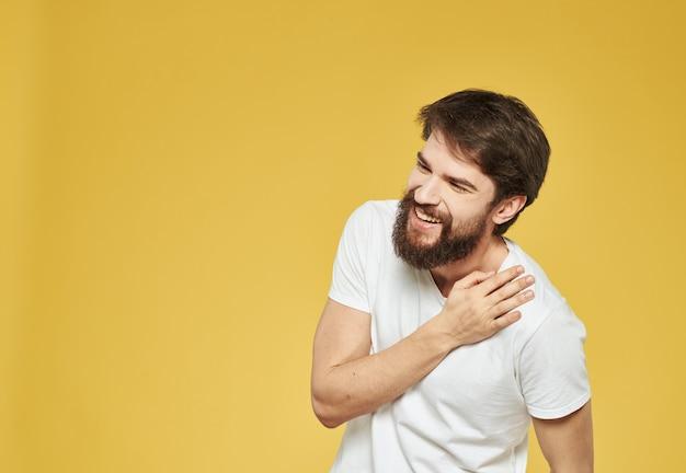 Żółta ściana model biała koszulka zbliżenie brunetka wąsy broda
