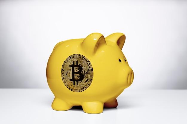 Żółta skarbonka z symbolem bitcoin z boku, na białym tle.