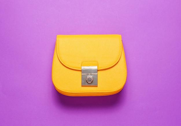Żółta skórzana mini torebka na niebieskiej powierzchni