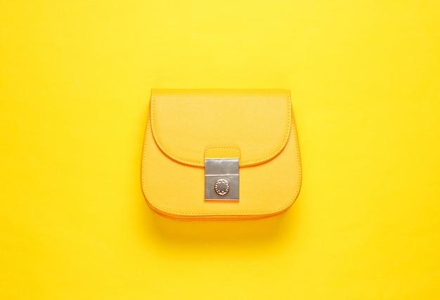 Żółta skórzana mini torebka na żółtej powierzchni