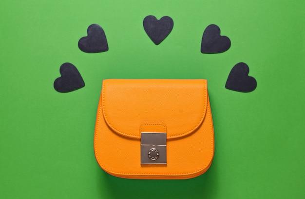 Żółta skórzana mini torebka z ozdobnymi czarnymi serduszkami na zielonym tle. minimalizm, moda i koncepcja miłości, czarny piątek. widok z góry