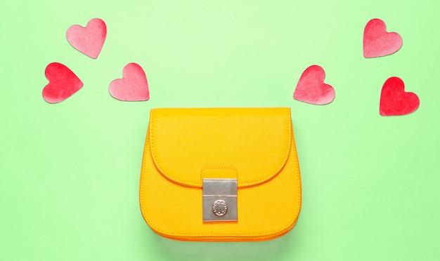 Żółta skórzana mini torebka z ozdobnymi serduszkami na zielonym tle. minimalizm koncepcja mody i miłości. widok z góry
