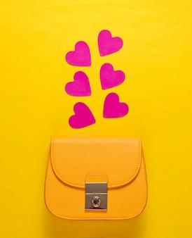 Żółta skórzana mini torebka z ozdobnymi serduszkami
