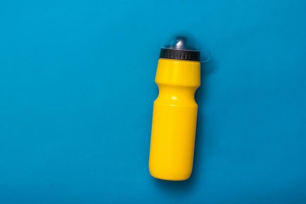 Żółta sportowa butelka wody na żółtym tle. akcesoria fitness.