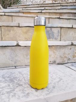 Żółta stalowa butelka na schodach z bliska