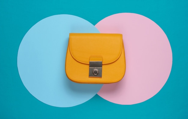 Żółta stylowa skórzana torebka na tle z niebiesko-różowymi pastelowymi kółeczkami. widok z góry. minimalistyczna moda martwa