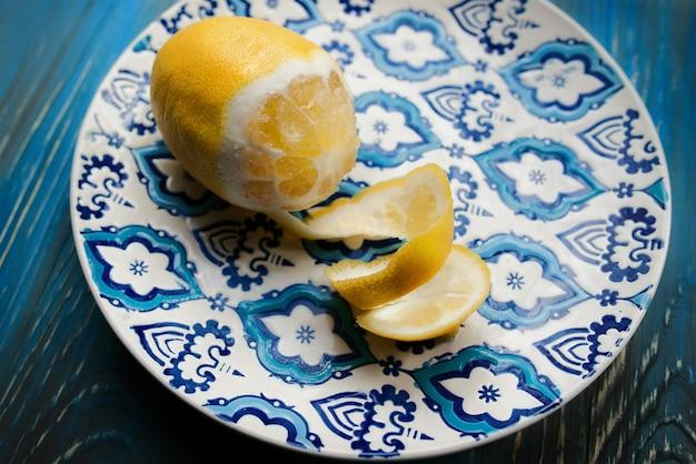Żółta świeża cytryna na orientalnym talerzu z niebieskim wzorem na drewnianym tle