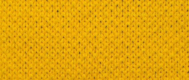 Żółta syntetyczna dzianina z bliska. dzianiny tekstura tło