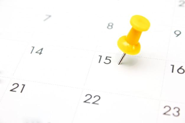 Żółta szpilka na białym kalendarzu zbliżenia strzale
