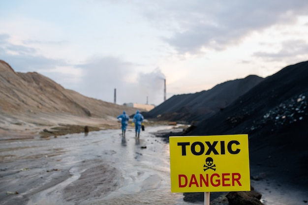 Żółta tablica z zapowiedzią obszaru toksycznego i niebezpiecznego na tle dwóch współczesnych naukowców w niebieskich kombinezonach ochronnych