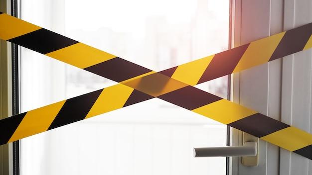 Żółta taśma koronawirusa zostań w domu. drzwi zaklejone taśmą. niebezpieczeństwo infekcji. kwarantanna
