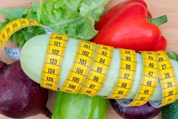 Żółta taśma pomiarowa i warzywa na drewnianej desce do krojenia. dieta zdrowego stylu życia.