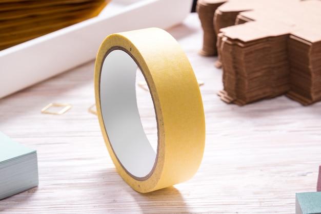 Żółta taśmy rolka na drewnianym biuro stole