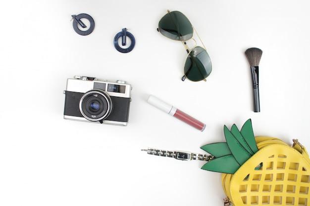 Żółta torebka ananasa otwiera się na białym tle z kosmetykami, akcesoriami, zegarkami, okularami przeciwsłonecznymi i kamerami. leżał płasko.