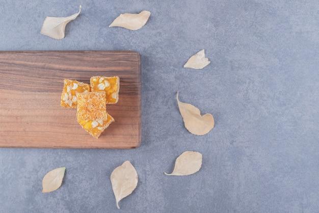 Żółta tradycyjna turecka rozkosz z orzeszkami ziemnymi na drewnianej desce do krojenia.