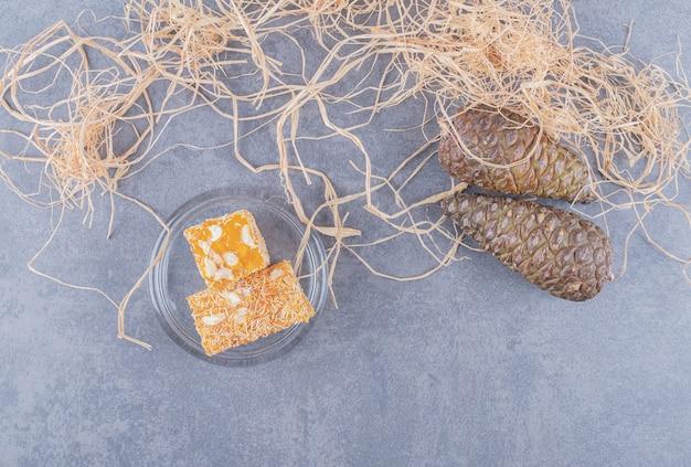 Żółta tradycyjna turecka rozkosz z orzeszkami ziemnymi na szarym tle.