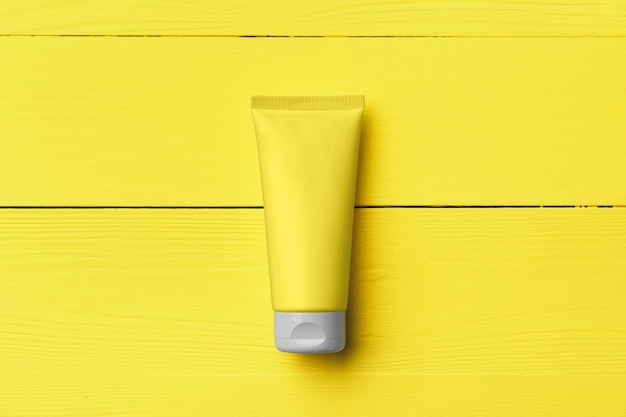 Żółta tubka kremowa na żółtym tle drewnianych