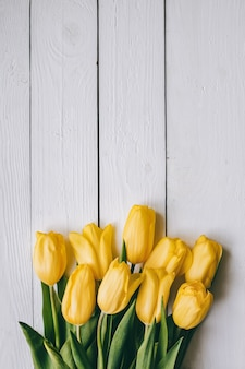 Żółta tulipan wiązka na białych drewnianych desek stajni nieociosanym wiejskim stołowym backgropund. puste miejsce na literę, tekst, litery, napis. piękny pionowy płasko świeckich szablon pocztówka.