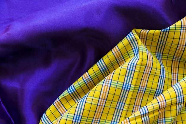 Żółta w kratkę deseniowa tkanina na prostej błękitnej tkaninie