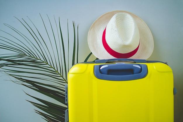 Żółta walizka, kapelusz i gałąź palmowa na wakacyjną wycieczkę