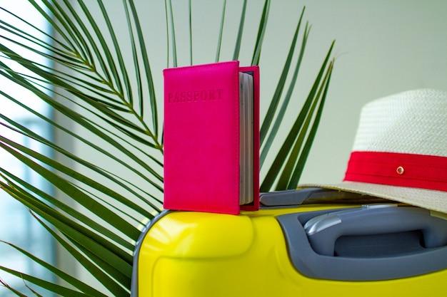 Żółta walizka z paszportem turystycznym