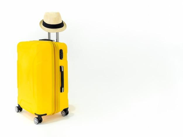 Żółta walizka ze słomkowym kapeluszem na białym tle.