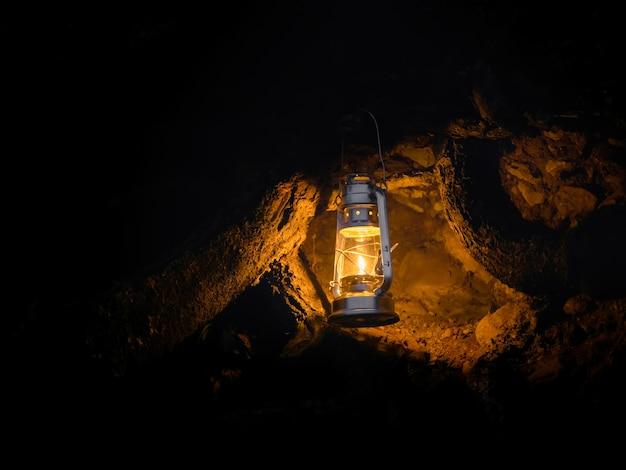 Żółta wisząca latarnia przy wejściu do jaskini