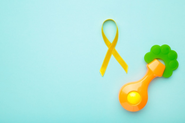 Żółta wstążka świadomości i zabawka dla dzieci na niebieskim tle pastelowych z miejsca na kopię.