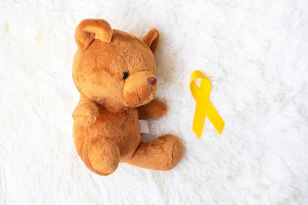 Żółta wstążka z lalką miś na białym tle do wspierania życia i choroby dziecka. miesiąc świadomości raka u dzieci we wrześniu i koncepcja światowego dnia walki z rakiem