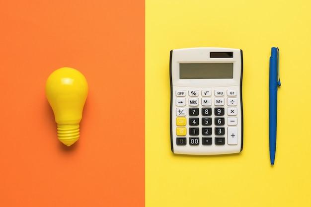 Żółta żarówka, kalkulator i niebieski długopis na pomarańczowym i żółtym tle.