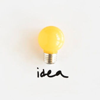 Żółta żarówka z pomysłu tekstem na białym tle