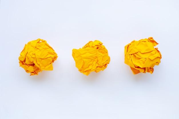 Żółta zmięta papierowa piłka odizolowywająca na bielu